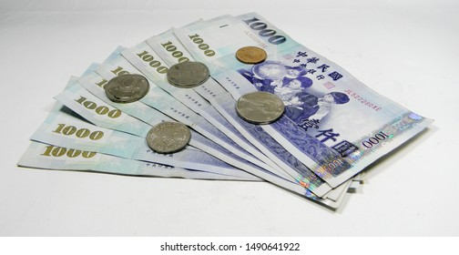 Banknotes of NT 1000 with coins, on white background