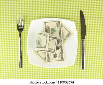 Banknotes on the plate on green tablecloth close-up
