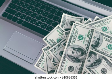 Banknotes over laptop keyboard