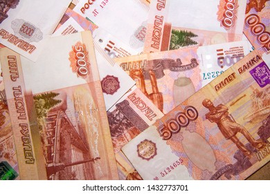 Banknotes of Russian currency face value of 5,000 rubles scattered on the table are a sign of riches and prosperity.