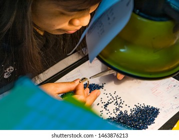 Bankok, Thailand - January 9, 2008: female goldsmith prepares a ring with gemstones. Manlyfemale people work in factories preparing jewellery for tourists.