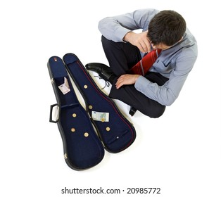 Bankrupt businessman sitting by a violin case with some change - isolated