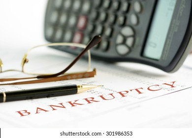 Bankruptcy concept image of a pen, calculator and reading glasses on financial documents.
