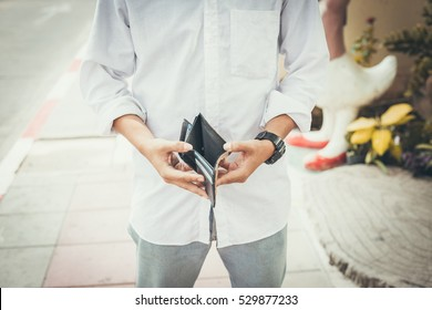Bankruptcy concept.Man in white shirt holding an empty wallet.color filter
