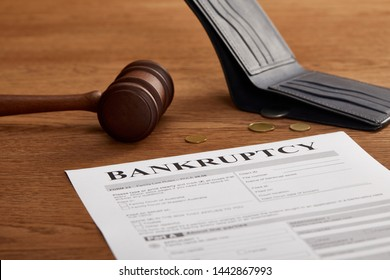 bankruptcy form with wooden gavel, coins and wallet on brown wooden table