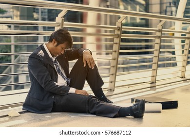 Bankruptcy man sitting on the floor, feeling disappointed on his business
