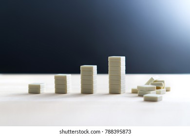 Bankruptcy, recession, inflation and business going down and collapse concept. Total breakdown and failure after growth. Company having bad luck. Going bankrupt. Stack of tiles crashing and falling.
