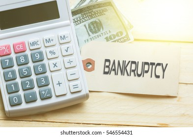 BANKRUPTCY Words on tag with dollar note and calculator on wood backgroud,Finance Concept