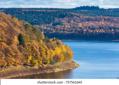 Banks of Gileppe lake with colorful foliage on trees, Belgian Ardennes, Liege province