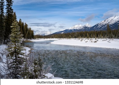 Banks of the Kootenay River in British Columbia Canada in Kootenay National Park during winter. Snow capped mountains in distance