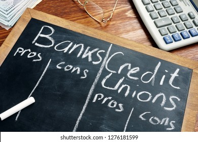 Banks vs. Credit Unions pros and cons written on a blackboard.