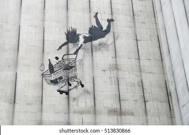 Banksy graffiti on the side of a disused office block in Central London showing a woman shopper falling with her shopping trolley.