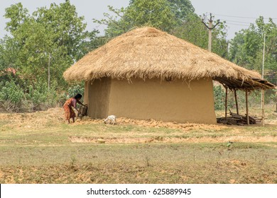 Bankura, West bengal,India.April 22, 2017. An unidentified village woman is working outside her mud house.
