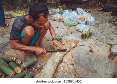 Banlung, Cambodia - December 11, 2018. Local bushman carves bamboo cups with local a machete.