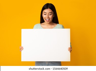 Banner for advertising. Joyful girl holding empty board over yellow studio background, copy space