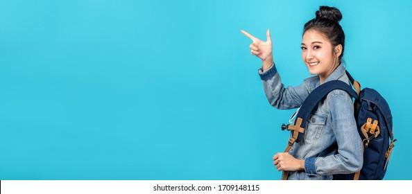 青の背景にコピー用スペースを指す手を指すアジア人女性旅行用バックパッカーのバナー。カジュアルジーンズのシャツと指を着て微笑むかわいいアジアの女の子が、現在のプロモーションのために脇を指差す。