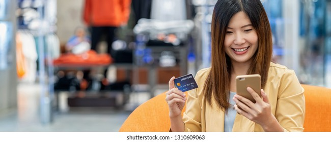 banner of Asian woman using credit card with mobile phone for online shopping in department store over the clothes shop store, technology money wallet and online payment concept, credit card mockup