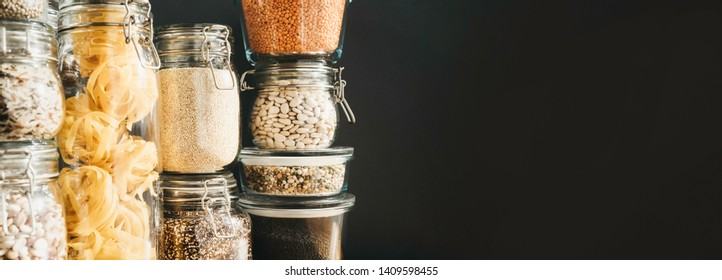 Banner with assortment of grain products and pasta in glass storage containers on wooden table. Healthy cooking, clean eating, zero waste concept. Balanced dieting food. Copy space.
