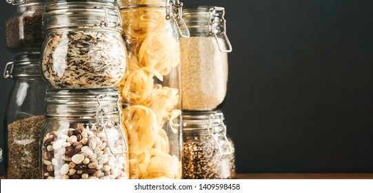 Banner with assortment of uncooked grains, cereals and pasta in glass jars on wooden table. Healthy cooking, clean eating, zero waste concept. Balanced dieting food. Copy space.