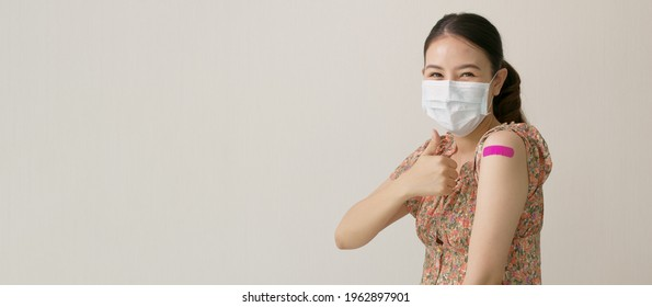 Banner attractive beautiful asia female or teenage receive covid-19 anti virus vaccine in campaign vaccination safe life happy smile cheerful with blue, yellow, pink bandage on arm with copy space.