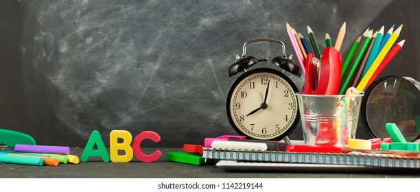 Banner Back to school Accessories for school on a dark background Pencils Plasticine letters Letters Alarm clock Briefcase Chalk Copy space