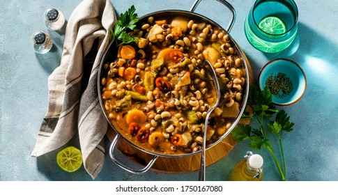 banner of Black-eyed Pea Vegan Chili in a metal pan on a wooden stand on a blue background