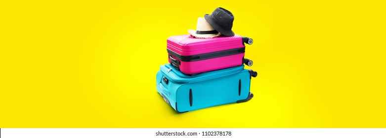 Banner Blue and Pink Trunks Summer Straw and Fabric Hats Two Suitcases Luggage Travel Things Concept Holiday Adventure Trip Isolated on Yellow Background