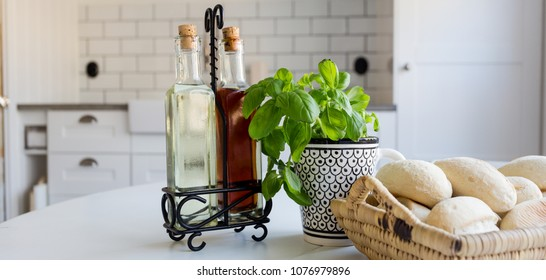 banner of bread, herbs and vinegar oil bottles on table with kitchen interior in the background