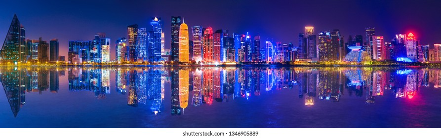 Banner of capital city of Qatar by night. Doha West Bay skyline mirroring in Doha Bay. Panorama of glassed skyscrapers of Doha, Qatar, Middle East, Arabian Peninsula in Persian Gulf. Night urban scene