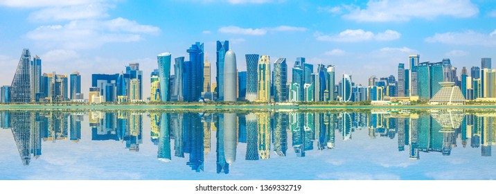 Banner of capital city of Qatar. Doha West Bay skyline reflecting in Doha Bay. Panorama of glassed skyscrapers of Doha, Qatar, Middle East, Arabian Peninsula in Persian Gulf. Sunny day.