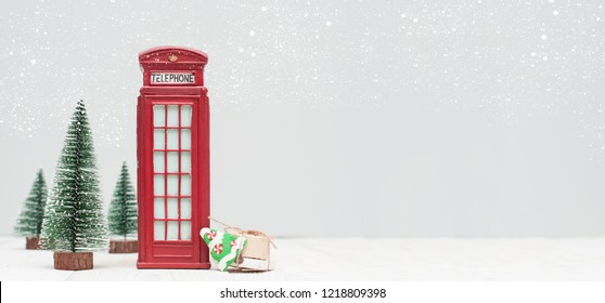Banner with christmas decorations, toy red phone booth, trees, gifts on light background