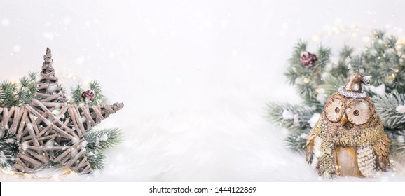 Banner with Christmas stars, decorative bird owl  and branches fir tree on  white  fur  background. Decorative christmas composition. Selective focus. Place for text.