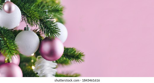 Banner with Christmas tree decorated with white and pink seasonal tree ornament baubles on pink background with empty copy space