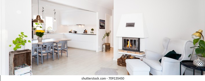 banner of a clean stylish living room interior with lit fire in fireplace and kitchen in the background