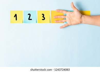 Banner counting 1-2-3. Collection of different colored sticky note papers with curled corner, open palm hand hidden three notes and empty three notes.