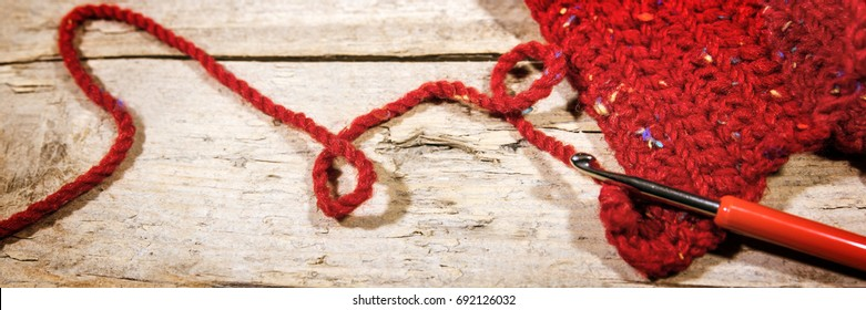 Banner, Crochet hook and red scarf on wooden table, handiwork and fashion