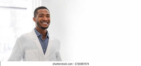 Banner for dental clinic. Portrait of young black guy dentist posing in clinic, panorama with copy space