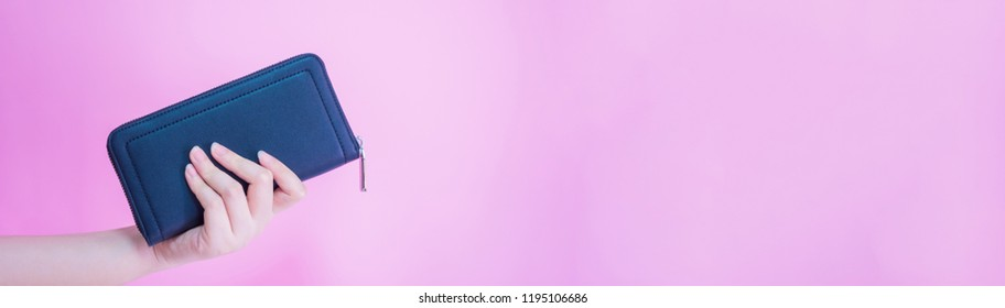banner design for black friday sale concept from left woman hand hold her blue purse with clipping path and pink pastel background