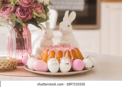 Banner. Easter cake, rabbits and eggs in the form of a unicorn and with a gold pattern on a white table. Copy space for text.