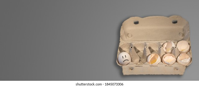 Banner with eggs packaging carton box with 5 broken chicken eggs and one not, with drawn unhappy face on it. Design concept for uncertainty, fate, fear, cruelty of life, unavoidable sacrifices