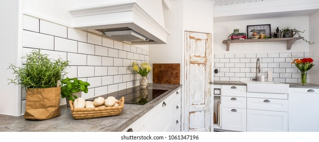 Banner of a fancy kitchen with rustic door white cupboards bread and Fresh herbs on the kitchen counter top
