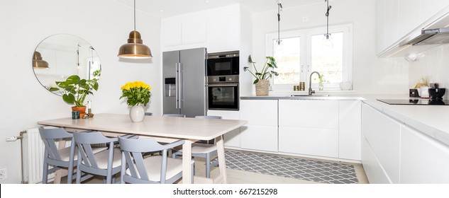 banner of fancy kitchen with yellow roses in a vase on the kitchen table