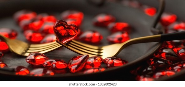 Banner. Festive table setting.Heart on a fork close-up. Holiday concept. Valentine's Day. Copy space for inscriptions.