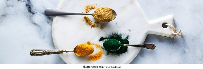 banner of ginger and turmeric powder and hawaiian spirulina in tablespoons on the board and white marble table. healthy supplements, superfoods in cooking