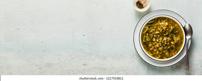 banner of gluten free green minestrone with cannellini beans. on the table with spices and arugula pesto. Traditional Italian Tuscan soup. healthy food for the whole family on the blue table