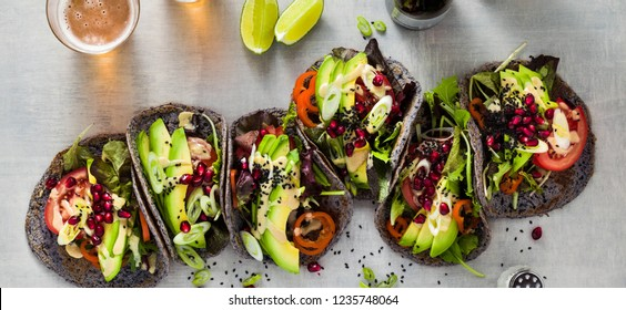 banner of Gluten-free vegan tacos from black bean  with tomato and avocado salad  with tahini sauce and pomegranate seeds. healthy fast food for the whole family or party and beer