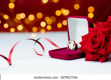 Banner. Gold ring, wedding ring in red box and , red rose on white-red background with beautiful bokeh. The moment of a wedding, anniversary, engagement, or Valentine's Day. Happy day.