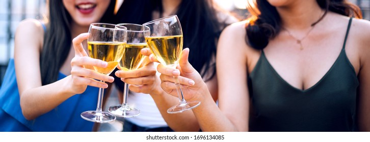 banner group happy Asian girl friends celebrating party with beer bottle toasting drinks at rooftop cafe in sunset together, night lifestyle after self quarantine of young people, Focus on glasses