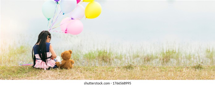 Banner Happy Child hug teddy bear hold air balloon green park playground. Teddy bear best friend little girl. Autism happy play together holding colorful helium balloons on playground with copy space