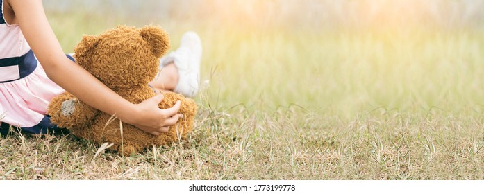 Banner Happy Child hug teddy bear in green park playground. Teddy bear best friend for little girl. Autism happy playing together on playground in happiness family feel love warm hugs with copy space